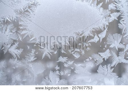 Christmas background. Frosty pattern in form of spot and beautiful pointed snowflakes around it on winter window pane. Selective focus.