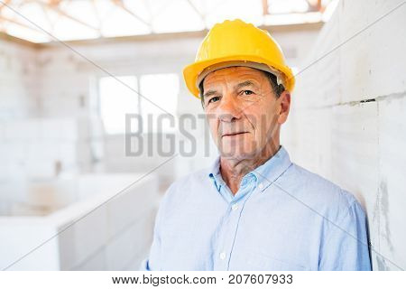 Senior architect or civil engineer in yellow helmet on the construction site.