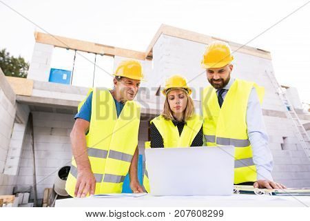Architect, civil engineer and worker with a laptop, discussing issues at the construction site.