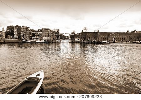 Boat on the canal of Amsterdam in historic city centre. Amsterdam drawbridge in closed position while the water-bus is approaching to it. Vintage Style Sepia photo