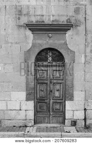 Building with traditional maltese door in historical part of Valletta. Entrance to an old house on the island of Malta. Black and white picture