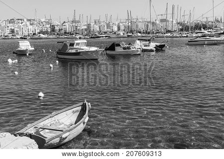 Yachts docked at the port of Malta. Boats moored in a row on the background of modern city. A shabby old boat among the luxury ships. Black and white picture