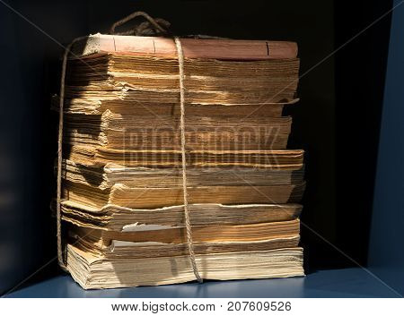 Stack of old yellowed and worn books and papers tied with string on bookshelf