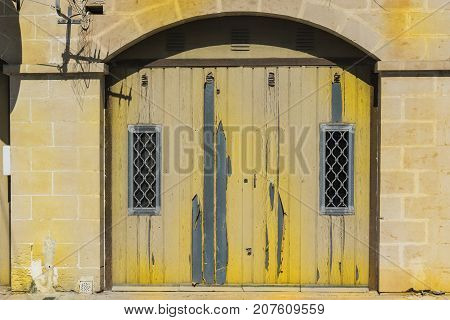 Flaked gate in historic part of Valletta. Entrance to an abandoned house on the island of Malta