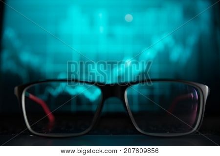 glasses in front of laptop with diagram on it concept