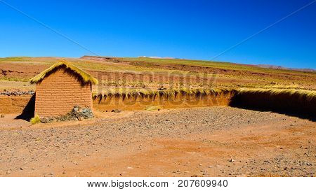 Landscape of southern Altiplano with clay brick wall and small hut, Andes, Bolivia.