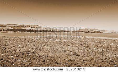 Plowed Shore of the Lake Lago di Ogliastro on the Background of the Mount Etna in Sicily Vintage Style Sepia