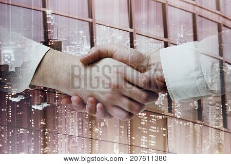 Side view and close up of handshake on night city background. Teamwork concept. Double exposure