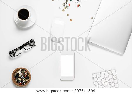 Top view and closeup of white office desktop with empty mobile phone coffee cup supplies laptop keyboard and other items. Mock up