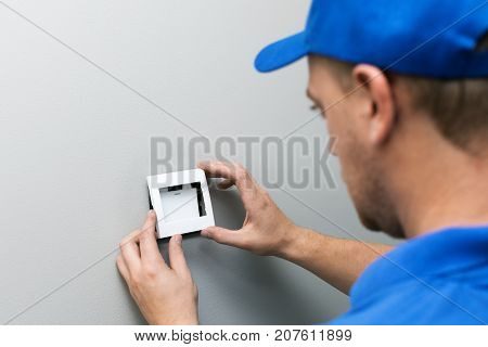 electrician in blue uniform installing light switch on the wall