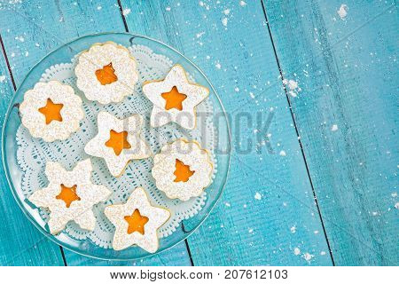 Christmas Linzer cookies with apricot jam on a blue wooden background.