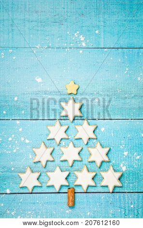 Traditional German Star Cookies in the shape of a Christmas tree over a blue background.