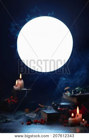 Magical Books And Candles In A Dark Still Life With Full Moon. Halloween Concept With Smoke. Spooky