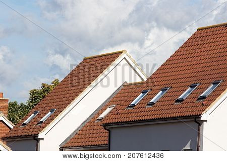 Skylight attic windows on modern clay tile roof. New residential building rooves with safety escape exit windows.