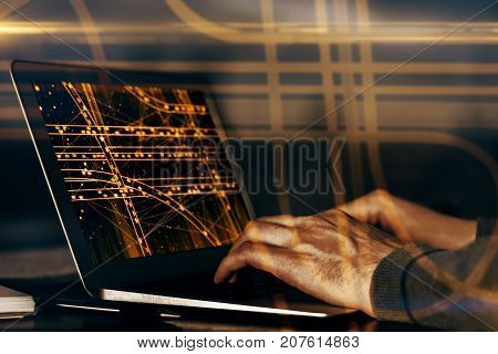 Side view of male hands at desk using laptop with abstract transport network on screen. Taxi app concept. Double exposure