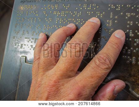 The hand touches the metal plate written in the Braille letters. This helps the blind to recognize and communicate through the text.