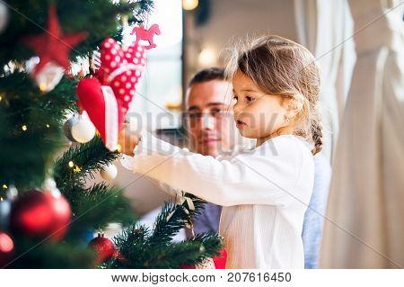 Young father with his little daughter at home decorating Christmas tree together.