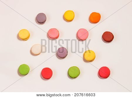Colorful sweet macaroons pattern on beige background