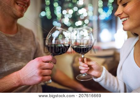 Beautiful young couple sitting on the floor, drinking red wine. Christmas time.
