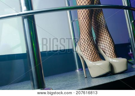 Sexy legs with fetish high heels shoes in the night club