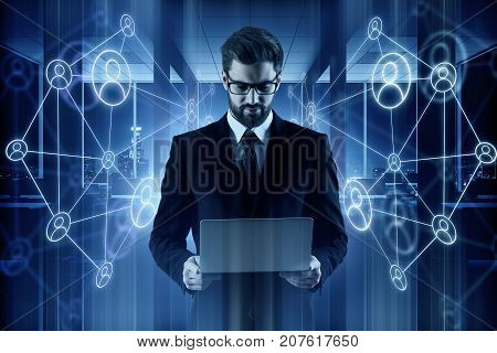 Handsome young businessman holding laptop in blurry office interior with business projections. Technology and HR concept. Double exposure