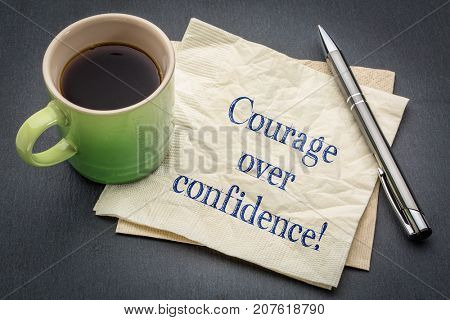 Courage over confidence! Handwriting on a napkin with cup of coffee against gray slate stone background