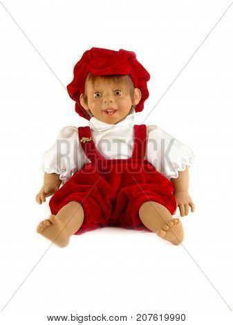 Cute little plastic baby doll with blue eyes sitting on empty background