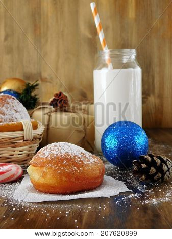 Donuts berliners and a glass of milk surrounded by Christmas attributes on a wooden background