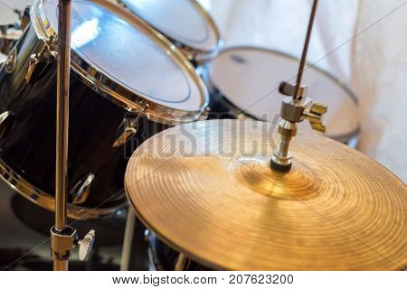 Closeup image of crash cymbal with blurred drums in background
