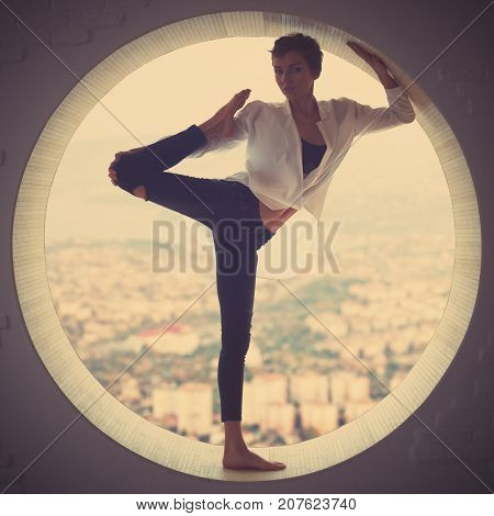 Beautiful fit yogi woman practices yoga asana Natarajasana - Lord Of The Dance pose in a round window with arial view of the city