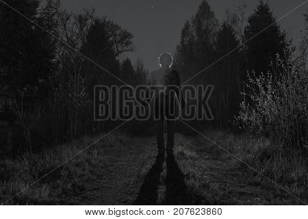 Male silhouette at the dark forest pathway through the bushes in the night. Man standing on the road against the car headlights. Mystery ghost concept. Black and white