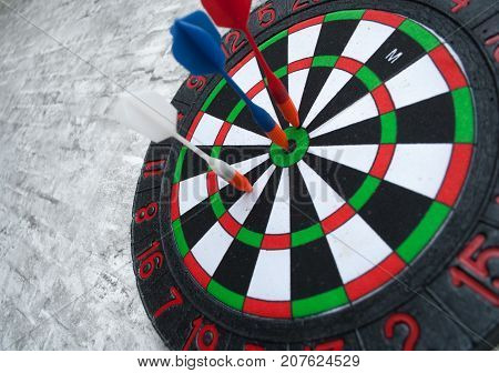 The Darts stick to the target, the Darts on the gray brick wall, closeup, concept of a successful enterprise
