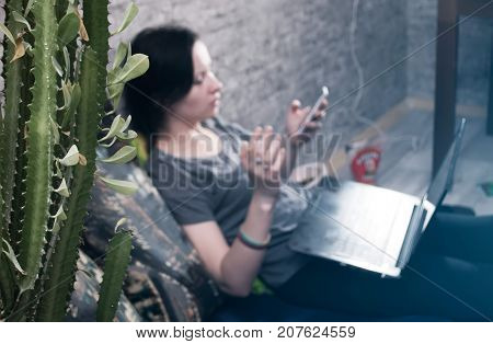 the cactus in the foreground, a young brunette girl in t-shirt and jeans, selective focus, lying on the bed in my bedroom to play video games on your smartphone, write letters, open the laptop
