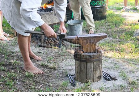 Blacksmith working metal with a hammer on the anvil in the forge. Outdoors scene