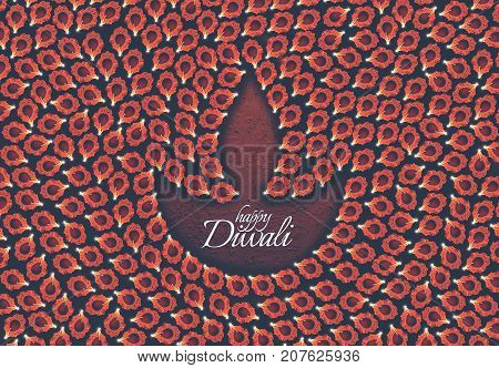 Stock photo of diwali greeting card showing top view of many illuminated diyas or oil lamps or panti forming shape of Diya with Happy Diwali text