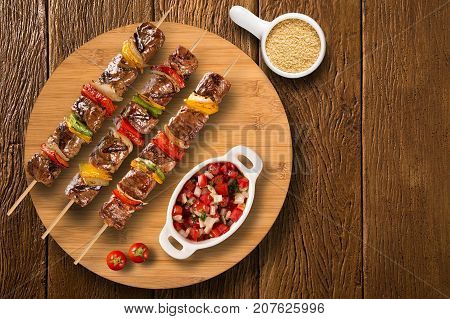Steak Skewers On Top Of A Board With Vinagrete And Corn Flour