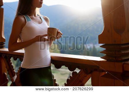 Slim caucasian woman holds cup of tea in her hands at mountain resort. Sports girl with hot coffee mug at wooden balcony of country house. Forest and mountains on background Dietary concept.