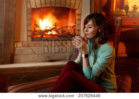 Woman is drinking tea and warming herself by the authentic fireplace. Young caucasian female holds cup of coffee at home. Warm house and cold fall concept.