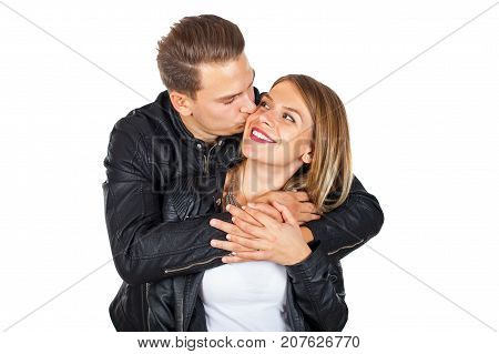 Happy young couple cuddling and kissing on isolated background