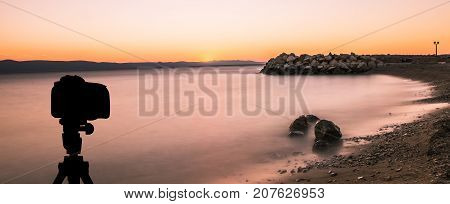 Camera on tripod with ocean and sunset in background / Podgora, Croatia
