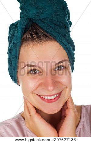 Close up beautiful young female with bath towel on head smiling at the camera on isolated background