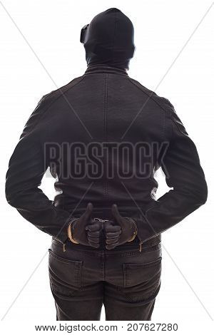 Back view angerous criminal wearing black clothes and mask with handcuffs on isolated background