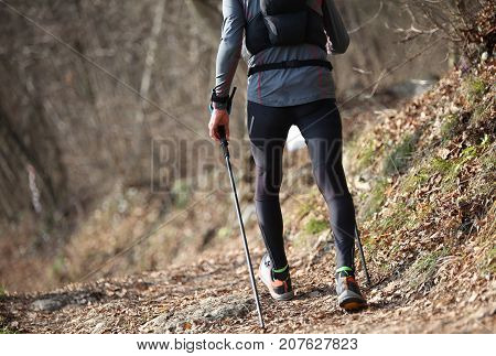 boy with poles Nordic walking during training in trail in the mountains