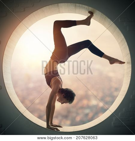 Beautiful sporty fit yogi woman practices yoga handstand asana Bhuja Vrischikasana - Scorpion handstand pose in a round window with arial view of the city at sunset.