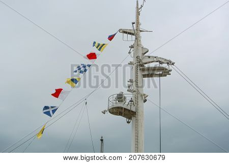 Colorful Signal Nautical Flags Against Cloudy Sky.