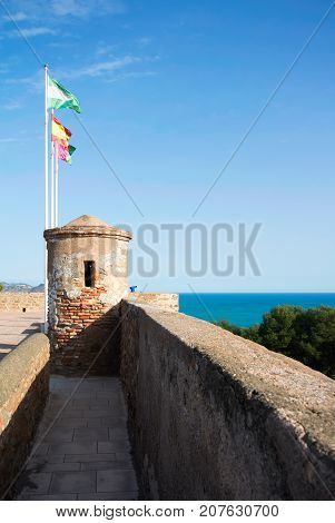 Bright Colorful Flags Over The Tover Of An Ancient Stone Wall Of Gibralfaro Castle (alcazaba De Mala