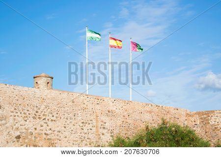 Bright Colorful Flags Over The Ancient Stone Wall Of Gibralfaro Castle (alcazaba De Malaga) Over The