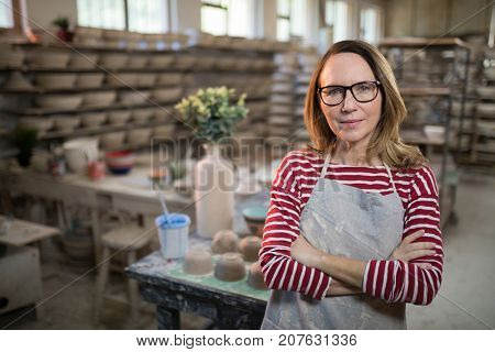 Confident female potter standing with arms crossed in pottery workshop