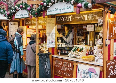 Prague, December 15, 2016: The seller offers customers a wide selection of honey and various wines. Christmas shop. Christmas shopping. Celebrating Christmas.