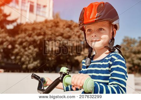 Boy in helmet standing with bike at autumn park. Happy active child
